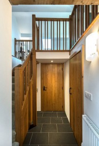 Hallway with door to garage and shower room on right. Stairs to mezzanine on left